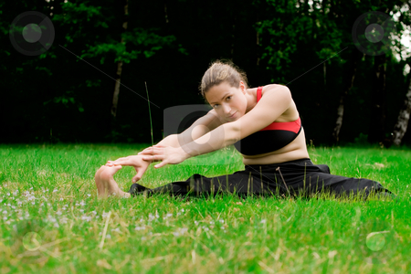 Practising yoga in a green field with trees stock photo, Young adult woman practising yoga on a field surrounded by trees by Frenk and Danielle Kaufmann
