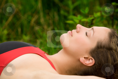 Sportive young adult resting in the grass of a meadow stock photo, Young woman resting in the grass after sports by Frenk and Danielle Kaufmann