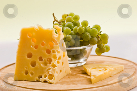 Piece of cheese stock photo, Piece of cheese on the board and grapes by Gennady Kravetsky