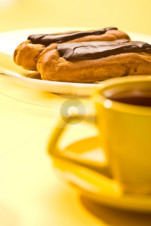 Chocolate eclair stock photo, Chocolate pastry filled with custard for dessert and yellow cup by Gennady Kravetsky