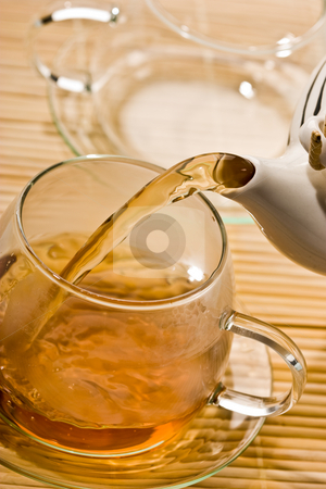 Tea stock photo, Food series: flowing golden tea into cup by Gennady Kravetsky