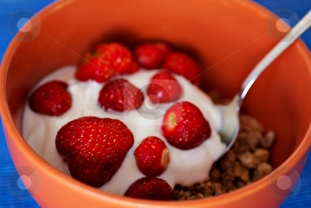 Cereals wtih strawberries and spoon stock photo, Cereals with yogurt and strawberries and metal spoon, shallow deep of field, blue background by Juraj Kovacik