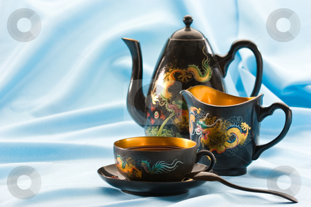 Tea-drinking stock photo, Teapot and cup filled with black tea by Gennady Kravetsky