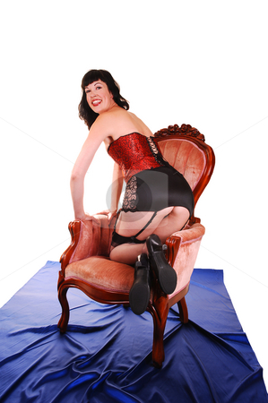 Woman in lingerie. stock photo, An tall young woman in red and black lingerie kneeling in the armchair on royal blue silk in the studio shooing her butt, for white background. by Horst Petzold