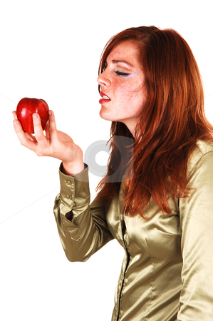 This apple is good. stock photo, Girl with red apple, long bright red hair in a close-up shoot and can not  wait to eat the apple. by Horst Petzold