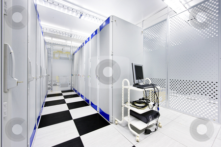 Datacenter stock photo, Clean suite in a data center with the perforated doors of server racks and a computer cart by Corepics VOF