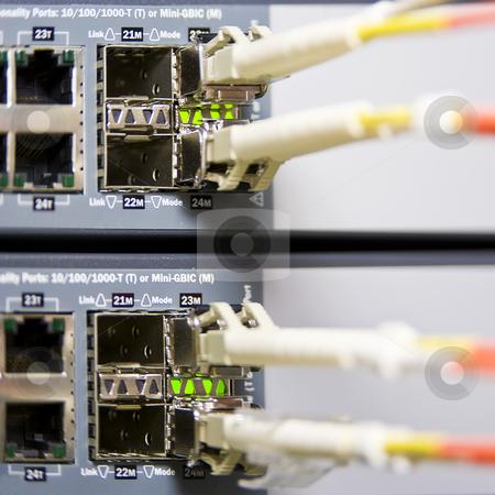 Fiber optics stock photo, Fiber optics connectors on an internet server by Corepics VOF