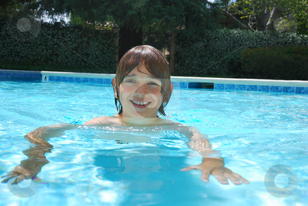 Smiling Teen Boy Swimming in Pool stock photo, Smiling teen boy swimming in the pool surrounded with white flower bushes in the background. by Denis Radovanovic