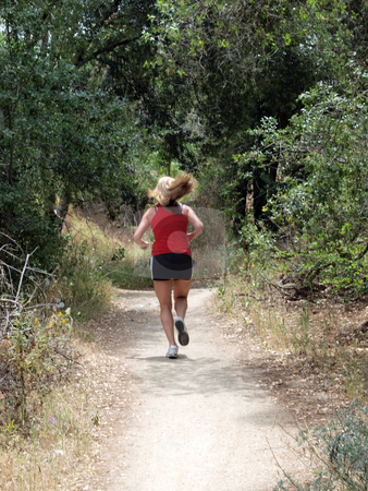 Young woman running down dirt trail from behind stock photo, Young blond woman running on dirt trail by Jeff Cleveland