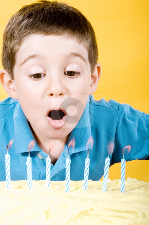 Birthday boy stock photo, Stock photo of boy blowing candles on cake over yellow background by iodrakon
