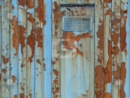 Rusty Blue Building stock photo, A rusty old metal building, flaking and peeling.  View of door and frame with vent. by Robert Gebbie