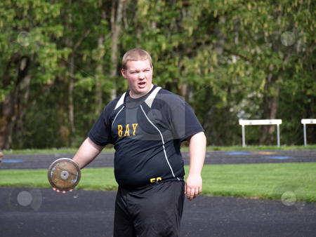 Teen Athlete with Discus stock photo, A teenage athlete holds the discus in one hand as he warms up for his toss. by Robert Gebbie