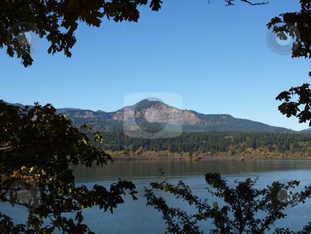 Mountain in Distance stock photo, Washington State landscape image of lake or river with mountain in background. Framed close by trees on the banks. by Robert Gebbie