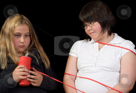 Tied Up stock photo, Two girl tying eachother up for fun, isolated against a black background by Richard Nelson