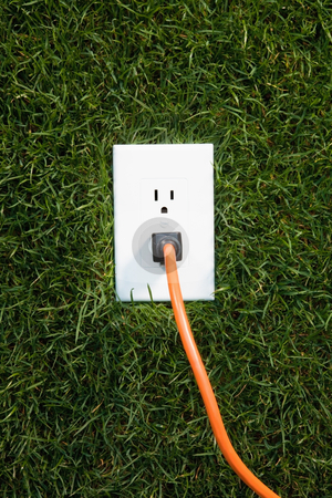 Electrical outlet in grass stock photo, Electrical outlet in grass with extension cord plugged in by Bryan Mullennix