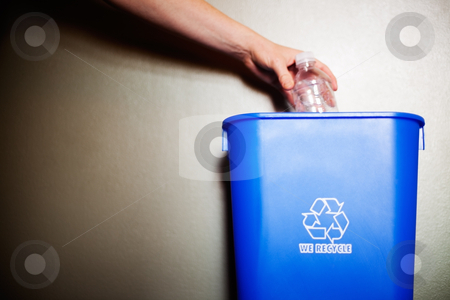 Arm dropping plastic bottling into recycling container stock photo, Woman's arm dropping plastic bottling into recycling container by Bryan Mullennix