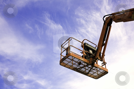 Orange construction lift against blue sky and clouds stock photo, Orange construction lift against blue sky and white clouds by Stephen Goodwin