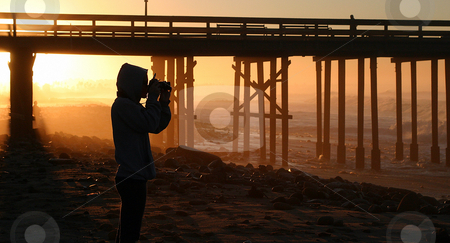 Photographer At Sunset stock photo, Photographer at sunset sunrise near the pier by the beach and ocean. by Henrik Lehnerer