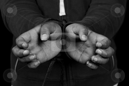 Slavery stock photo, Closeup view of someone's hands being tied against their will by Richard Nelson