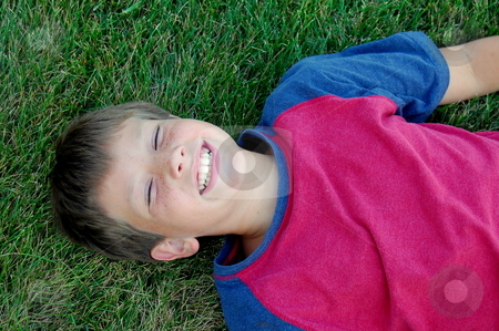 Boy lying in grass smiling stock photo,  by Heather Shelley