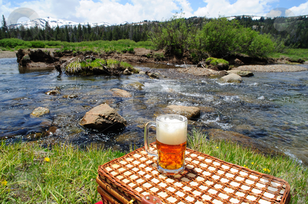 Ale And Nature stock photo, Partially consumed mug of ice cold  micro brewery Ale sitting on a picnic basket used for a table wth crystal clear river and forest in the background. by Lynn Bendickson