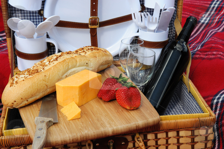 Cheese And Wine stock photo, Garlic frech roll, cheddar cheese, strawberries and a bottle of red wine in a wicker picnic basket with plaens and utensils. by Lynn Bendickson