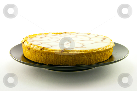 Bakewell Tart stock photo, Delicious looking iced bakewell tart on a black plate with a plain background by Keith Wilson