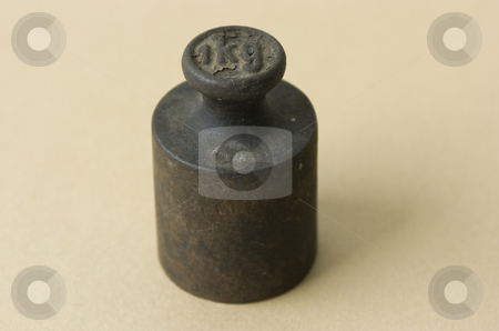 Single iron weight stock photo, Single old iron weight on beige background by Andreas Brenner