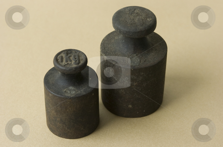 Two iron weights stock photo, Two old iron weights on beige background by Andreas Brenner