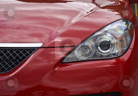 Automotive Headlight stock photo, Headlight of a red sports car. by Steve Carroll