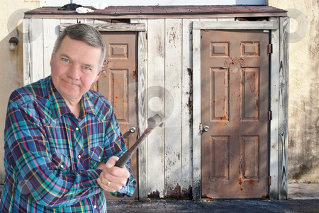 Mature handyman with hammer getting ready to tear down an old st stock photo, Mature handyman with hammer getting ready to tear down an old storage shed. by Steve Carroll