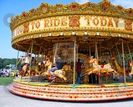 Fairground Carousel stock photo, People enjoying a ride on a colorful carousel at fairground by Robert Ford