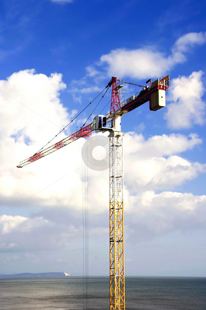 Tall Crane stock photo, Tall crane doing high rise work near seafront by Robert Ford