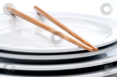 A pair of chopsticks on a stack of white plates stock photo, A horizontal close up of a pair of chopsticks on a stack of white plates by Vince Clements