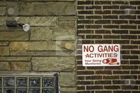 No gang activities sign stock photo, No gang activities sign against red brick and stone walls with security light by Stephen Goodwin