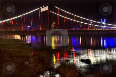 Jiangqun Bridge at Night Close Up with Reflections Fuxin China stock photo, Jiangqun Qiao, General Bridge, Fuxin City, Liaoning Province, China, Night Shot of Colored lights and reflections. Electricity in rural China. by William Perry