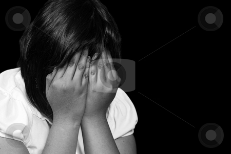 Crying Child stock photo, A young female child is covering her face and crying, post processed in black and white and isolated against a black background by Richard Nelson