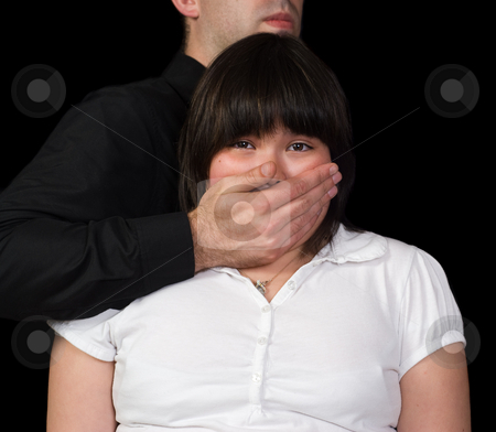 Kidnapped Child stock photo, Concept image of a child being kidnapped featuring a man standing behind a girl with his hand covering her mouth, isolated against a black background by Richard Nelson