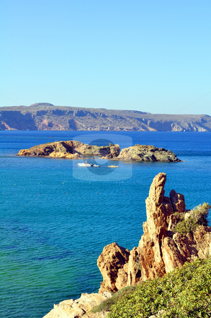 View of a small island in the Mediterranean Sea stock photo, Boat and small rock island in the Mediterranean Sea by Fernando Barozza