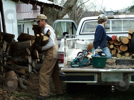 Father and Son stock photo, This father works with his son stacking wood for the cold winter months. by Krystal McCammon