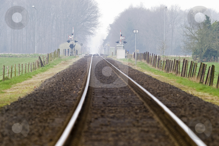 Railtrack with hazy crossing. stock photo, Railtrack with hazy crossing in the background. by Gert-Jan Kappert