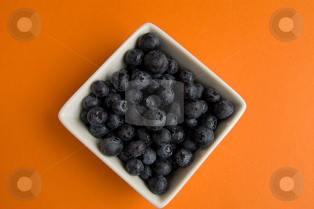 Blueberries in square white bowl  stock photo, Fresh blueberries in square white bowl on orange background by Christian Rhein