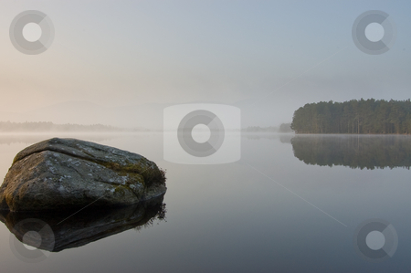 Tranquill lake in early morning mist stock photo, Calm lake mirror like in early morning mist by Christian Rhein
