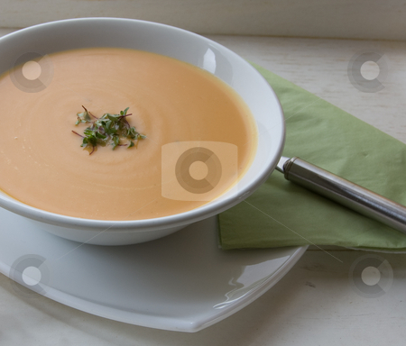 Sweet potato soup stock photo, 45 degree shot of soup in white bowl on rustic tray by Christian Rhein