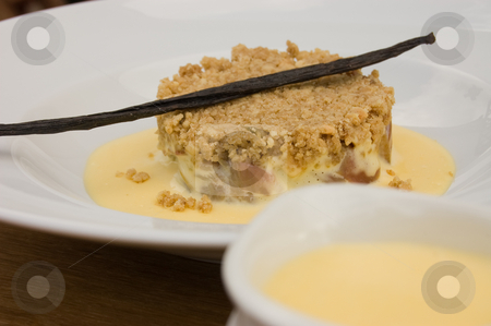Rhubarb crumble and custard stock photo, 45 degree shot of rhubarb crumble and custard in bowl plate on table with jug of custard partially showing by Christian Rhein