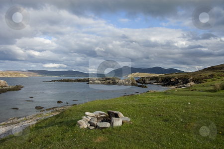 Wild camp on coast stock photo, Shot of fireplace on grassy ledge with sea  showing and mountain in background by Christian Rhein