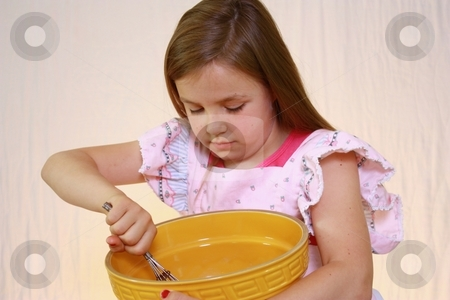Young cute girl with pink apron and mixing bowl.  stock photo, Young girl with mixing bowl by Gregory Dean
