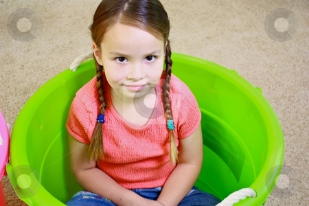 Young cute girl playing in green bucket stock photo, Young girl playing by Gregory Dean