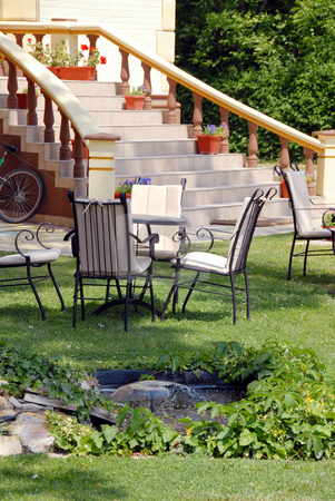 Home yard stock photo, House stairs  with flowerpots and tables on lawn in yard by Julija Sapic