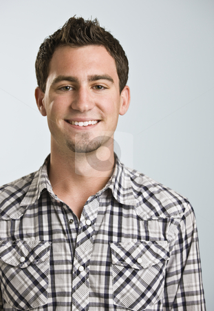 Attractive Young Man Smiling at Camera stock photo, A young man wearing a plaid shirt is smiling at the camera. by Jonathan Ross